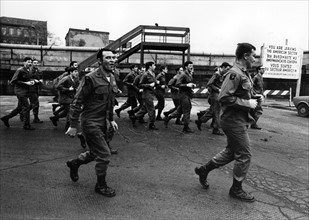US soldiers jogging in front of the Berlin Wall