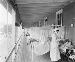 Masked Nurse at the Head of a Row of Beds Treating Patient during Influenza Pandemic, Walter Reed Hospital, Washington DC, USA, Harris & Ewing, 1918