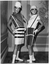 Two Fashion Models Wearing Sleek Interpretations of Andre Courreges' Suspender Outfits Featuring Barrel Skirts with Button-Attached Suspenders and Leather Cowl-Neck Blouses, Presented by Samuel Robert...