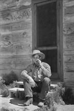 Cowboy Smoking in front of Bunkhouse, Quarter Circle U Ranch, Big Horn County, Montana, USA, Arthur Rothstein, Farm Security Administration, June 1939