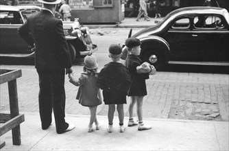 Father and three children waiting to cross the street