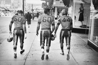 Rear View of Three High School Football Players in Uniforms walking down Street