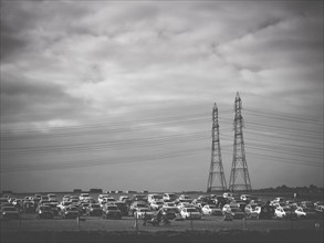 Multiple Cars Parked in Field with Electric Pylons in Background