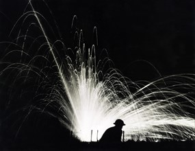 Silhouette of Soldier against Phosphorous Streamers from Bombs Exploding during Night Attack