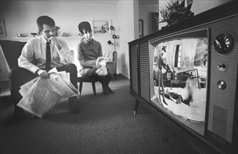 Man and Woman watching Film Footage of Vietnam war on Television in their Living Room