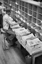 Worker sorting newspapers at Post Office, New York City, May 1957