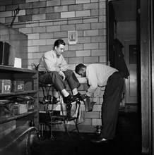 Greyhound Driver getting his Shoes shined by a Porter at the Garage, Pittsburgh