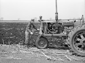Farmer cranking Tractor while planting Corn, Listing method