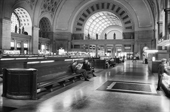 Passengers seated in long benches in the waiting room of Union Station, Washington