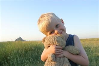 France, Normandie, Manche, baie du Mont-Saint-Michel, enfant de 4 ans Felix et doudou, ours en peluche, champ, personnage autorise,