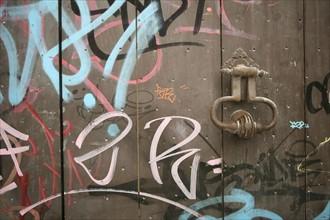 France, languedoc roussillon, gard, uzes, maison ancienne, heurtoir de porte et graffiti sur la porte, environnement, salete, pollution,