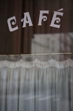 france, region ile de france, paris 7e arrondissement, rue de l'universite, devanture, facade d'un cafe, bar, rideau, lettrage. Date : decembre 2012.
