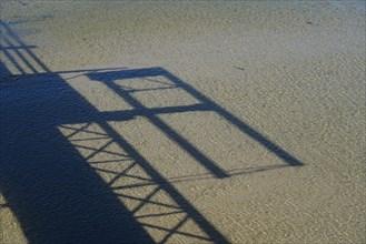 Ombre portée d'une passerelle sur le sable