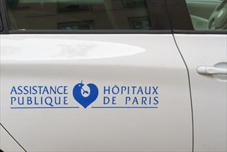 Logo de l'Assistance Publique Hôpitaux de Paris sur une portière de voiture