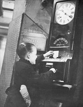 Young boy clocking on at the Trocadero Restaurant, Leicester Square, Westminster, London, c1939. Artist: Unknown
