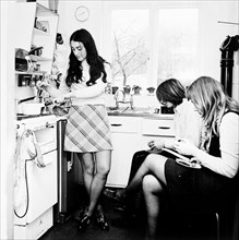 Three young people in the kitchen of a London flat, c1960s. Artist: Henry Grant