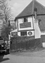 Kitty Brunell's Standard 16 outside Ye Olde Fighting Cocks inn, St Albans, Hertfordshire, 1930s. Artist: Bill Brunell.