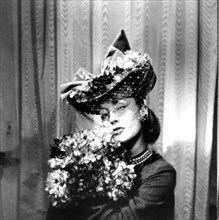 Woman wearing a hat with a veil, holding a bouquet of flowers, Paris, 1943. Artist: Unknown