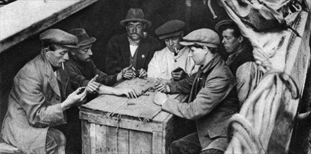 A bargee and his mates play dominoes in the hold of a canal boat, 1926-1927. Artist: Unknown