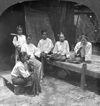 Burmese women smoking outside their home, Mandalay, Burma, 1908.  Artist: Stereo Travel Co