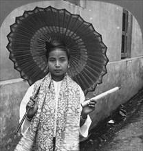 Young Burmese woman holding a huge cigar, Rangoon, Burma, 1908. Artist: Stereo Travel Co
