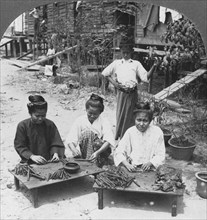Making the huge cigars smoked by women, Burma, 1908. Artist: Stereo Travel Co