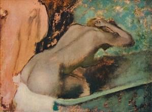 Femme assise sur le bord d'une baignoire et s'epongeant le cou, c1880, (1936). Artist: Edgar Degas