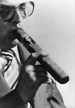 Smoking a 'François Mitterrand' cigar at a tobacco fair in Belgium, c1970s. Artist: Unknown