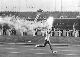 The Olympic flame entering the Olympic Stadium, Tokyo, 10 October 1964. Artist: Unknown