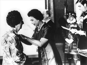 Queen Elizabeth II presents the BEM to Miss Margaret Aiken, Northern Ireland, 1977. Artist: Unknown