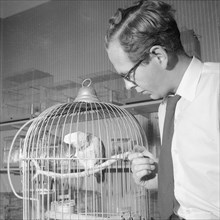 A man with a parrot in a pet shop, Landskrona, Sweden, 1959. Artist: Unknown