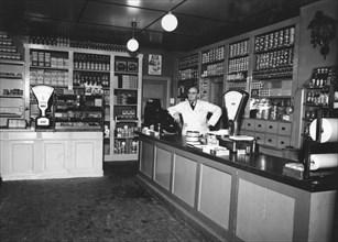 Owner Magnus Påhlsson in his grocer's shop, Sweden, 1943. Artist: Unknown