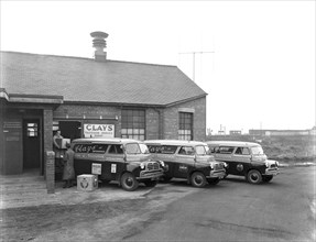 Austin vans being loaded outside Clays TV repair depot, Mexborough, South Yorkshire, 1959. Artist: Michael Walters