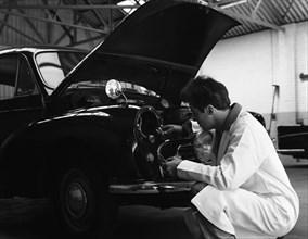 Auto electrician changing a light bulb on a Morris Minor, Nottingham, Nottinghamshire, 1961.  Artist: Michael Walters