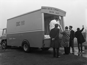 Traders buying bacon direct from a Danish Bacon wholesale van, Kilnhurst, South Yorkshire, 1961. Artist: Michael Walters