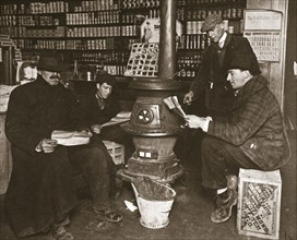 A group of men around a stove in a shop, USA, c1910. Artist: Unknown