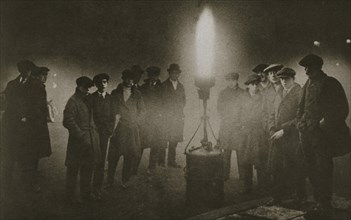 Gathering around an acetylene flare at a traffic control point in the fog, early 20th century. Artist: Unknown