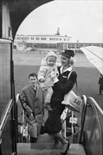 SAS stewardess carrying a baby onto a plane, Bulltofta airport, Malmö, Sweden, 1950. Artist: Torkel Lindeberg