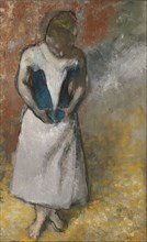 Woman standing from the front, clasping her corset, ca. 1883. Artist: Degas, Edgar (1834-1917)