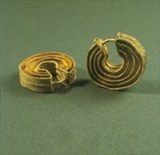 Two gold earrings spiral shaped from the treasure of the Foxardos.