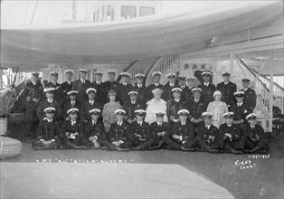 King George V and Queen Mary aboard 'HMY Victoria and Albert', with her crew, c1933. Creator: Kirk & Sons of Cowes.