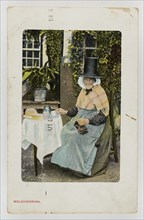 A Welsh woman at tea table with knitting on her lap, c1900.