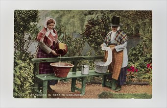 Cleanliness is next to Godliness.  Women in Welsh costume washing in tubs on bench, c1900s