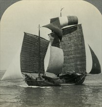 'Picturesque Chinese Junk under Full Sail on the Yellow Sea, Coast of Manchukuo in Distance', c1930s Creator: Unknown.