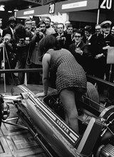 Female model climing in to Cooper F5000 at 1969 Racing Car show. Creator: Unknown.