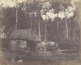 Charette devant l'entrée d'un abri au toit de chaume, 1850-53.