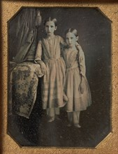 Two Identically Dressed Young Girls Standing Next to a Table, 1840s.