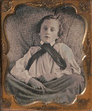 Boy Seated Cross-legged, Partially Covered by Blanket, Leaning Against Cushion, 1850s.