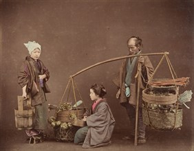 Two Japanese Women and One Japanese Man Posing with Water Bucket and Baskets], 1870s.