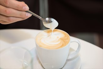 female hand holding a spoon over a hot cup of coffee Cappuccino